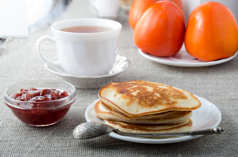 White plate with pancakes and vintage silver spoon. A cup of tea and strawberry jam on a gray textile background royalty free stock images