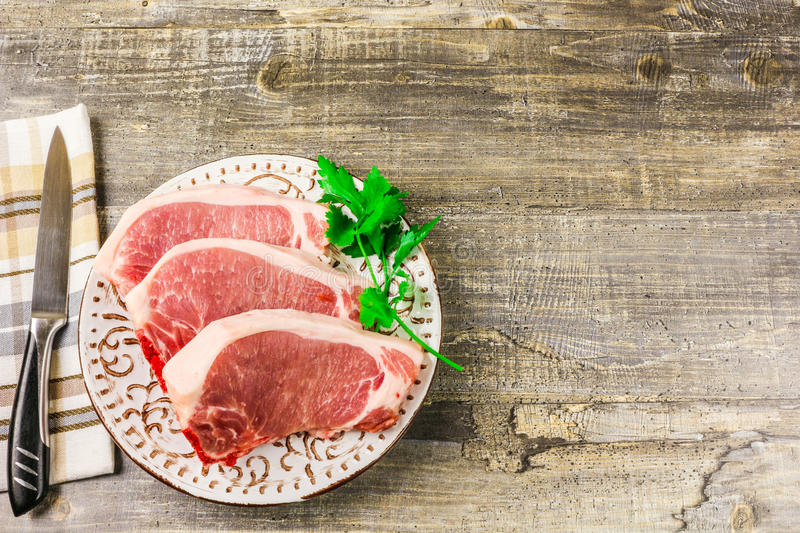 White plate raw sliced meat on wooden table, top view. Food, a knife, branches of greens royalty free stock photography