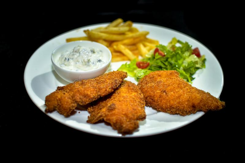 A white plate setup of delicious, crispy golden-brown fried Fish Fries stock image