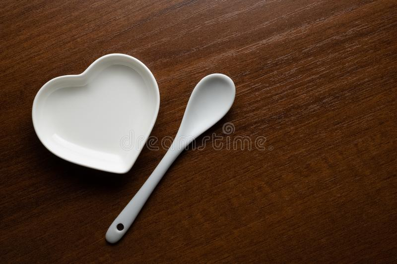 White plate in the shape of a heart and a spoon on a wooden table. Concept of Valentine`s Day or wedding romantic theme. Ceramic. White plate in the shape of a stock photos