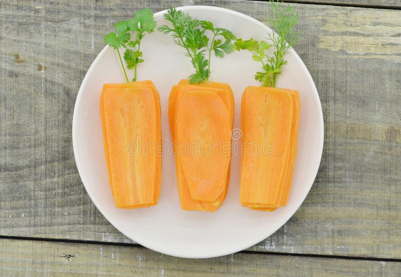 White plate with slices carrots and herbs on wooden table, closeup stock photo
