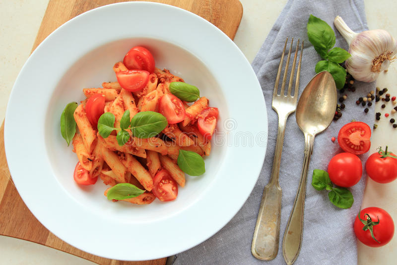 White plate with spaghetti pasta in tomato sauce with fresh basil royalty free stock image