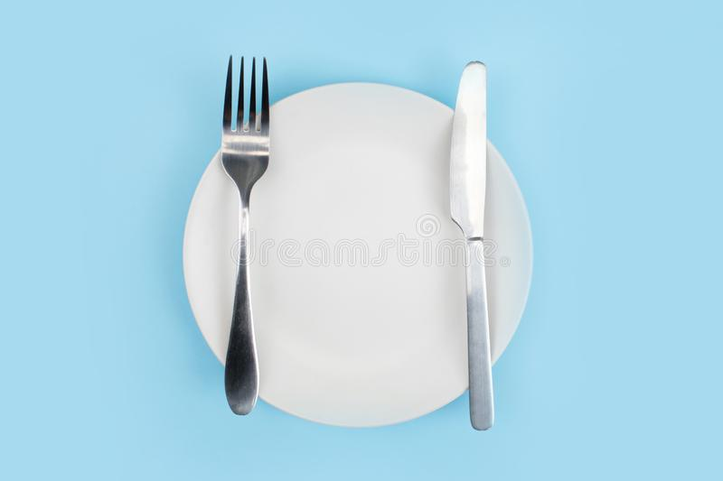 A white plate with a spoon on a blue background. Top view.  royalty free stock photo