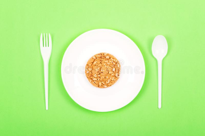White plate with spoon, fork and whole grain cookies oatmeal. Ketogenic Diet, weight loss, intermittent fasting, lunchtime concept. Minimal style, flat lay stock photos