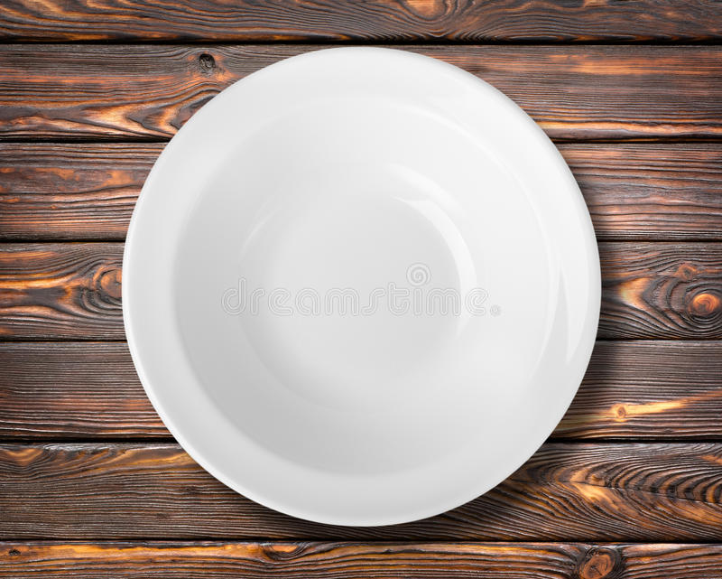 White plate on a table. White plate on a brown wooden table royalty free stock photography