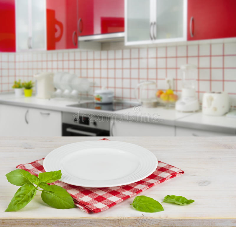 White plate on table over modern kitchen interior background royalty free stock images