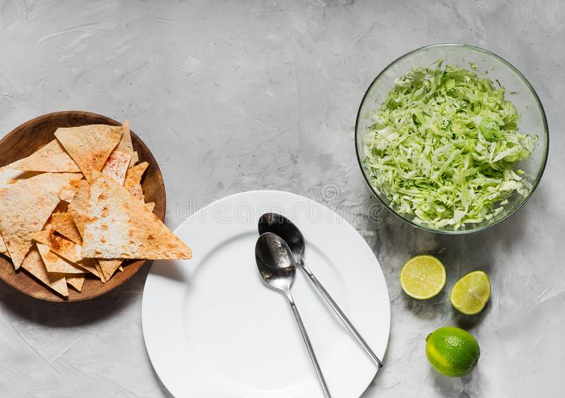 White plate with tablespoons, chips and salad from fresh cabbage with greens stock photography