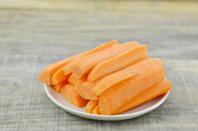 White plate with tasty carrots sticks on wooden table royalty free stock photography