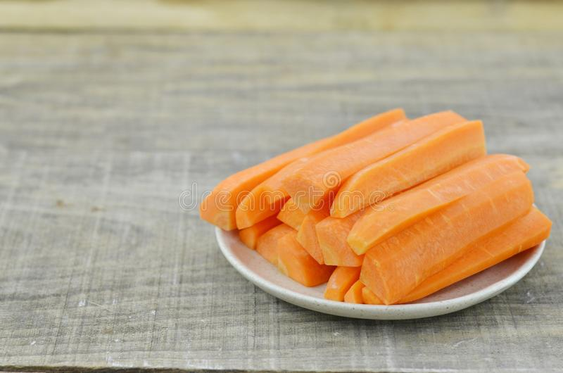 White plate with tasty carrots sticks on wooden table royalty free stock photos