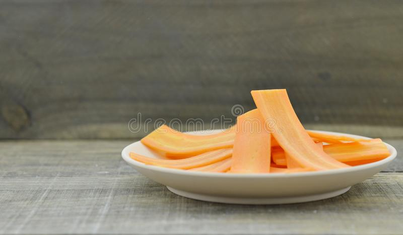 White plate with thin silce carrots on wooden table, closeup stock photo