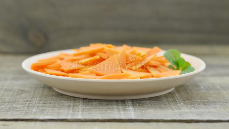 White plate with triangle slices carrots on wooden table royalty free stock image