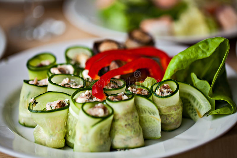 White plate of vegetable snacks.Eggplant cucmber. Rolls with pepper and lettuce stock images