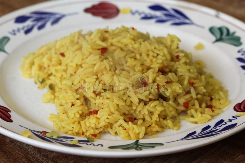 White plate with yellow Indian rice stock image