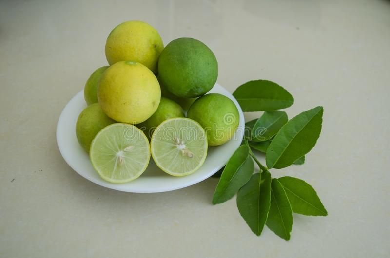 Plateful Of Key Lime. A white plate of yellow ripe, and green unripe key limes. One of the limes is cut in halves showing its inner pulp, seeds, segment, walls stock photos