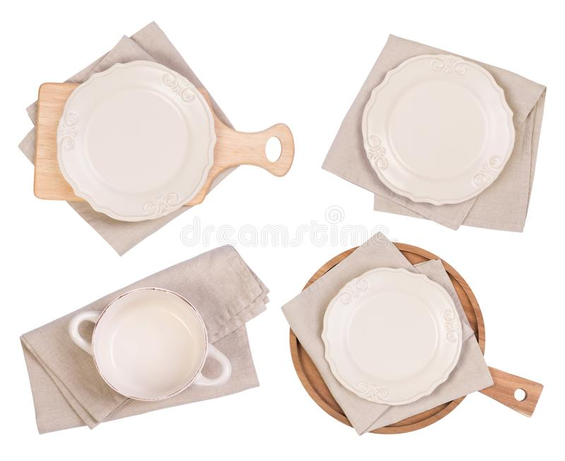 White plates, cutting boards and napkins isolated on white background, top view. Rustic white plates, cutting boards and napkins isolated on white background royalty free stock image