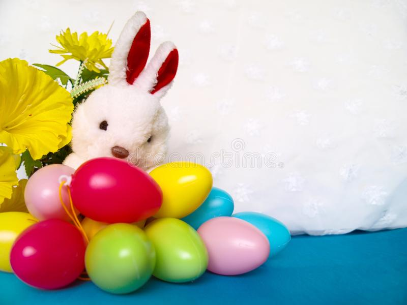 White plush rabbit with colorful Easter eggs and yellow flowers. stock image