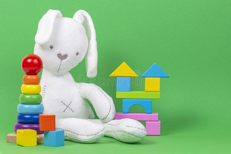White plush toy rabbit, baby stacking rings pyramid and colorful wooden blocks on light green background stock image