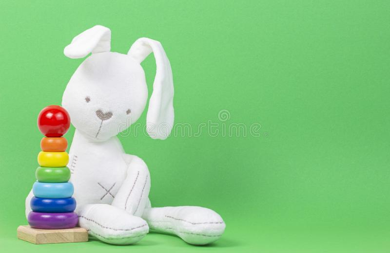 White plush toy rabbit with wooden baby stacking rings pyramid on light green background royalty free stock photos
