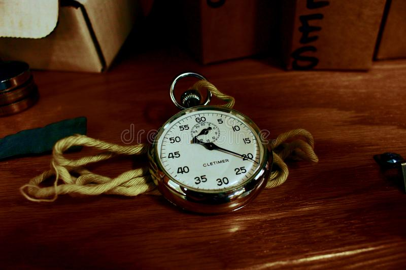 White Pocket Watch With Gold-colored Frame on Brown Wooden Board stock images