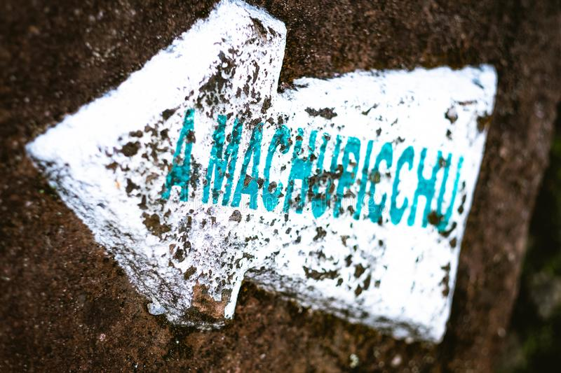 White pointing arrow sign to Machupicchu on the rock. Closeup of white pointing arrow sign to Machupicchu with blue label on the rock stock image
