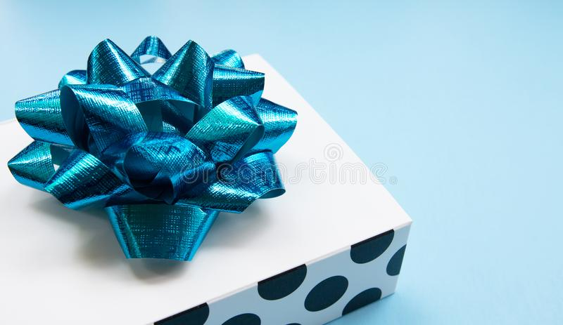 White polka dot gift box on a blue contrasted background, creating a romantic atmosphere. Typically used for birthday, a. Nniversary presents, gift cards, post stock photography
