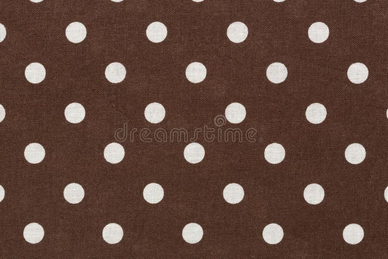 White polka dots on brown fabric background. stock photo