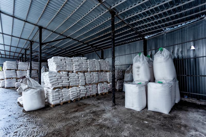 White polyethylene bags with factory products in warehouse stock images