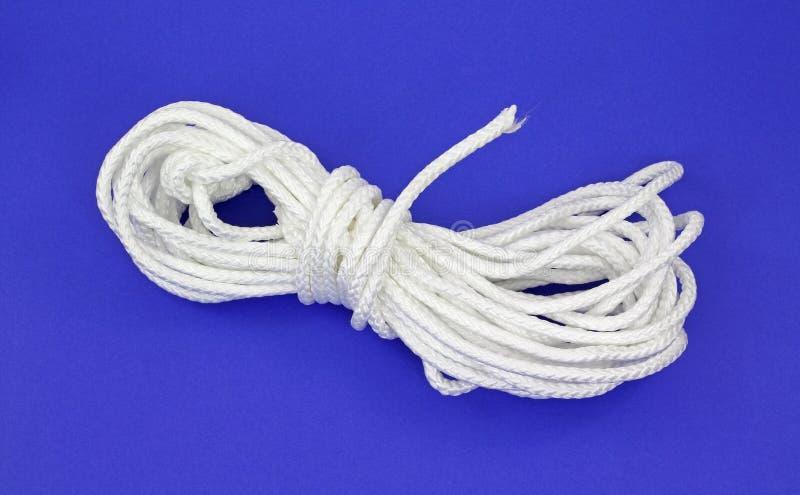 White polypropylene rope. A large length of white polypropylene rope on a blue background royalty free stock image