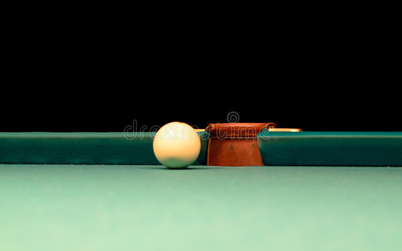White Pool Ball on Billiard Table Near the Hole. Close up White Pool Ball on Billiard Table Near the Hole at the Edge royalty free stock photo