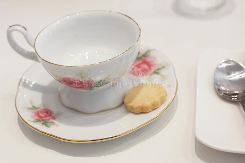 Porcelain antique tea cup with a cookie for afternoon tea. White porcelain antique tea cup and saucer with biscuit. Afternoon tea with beautiful vintage teacup stock images