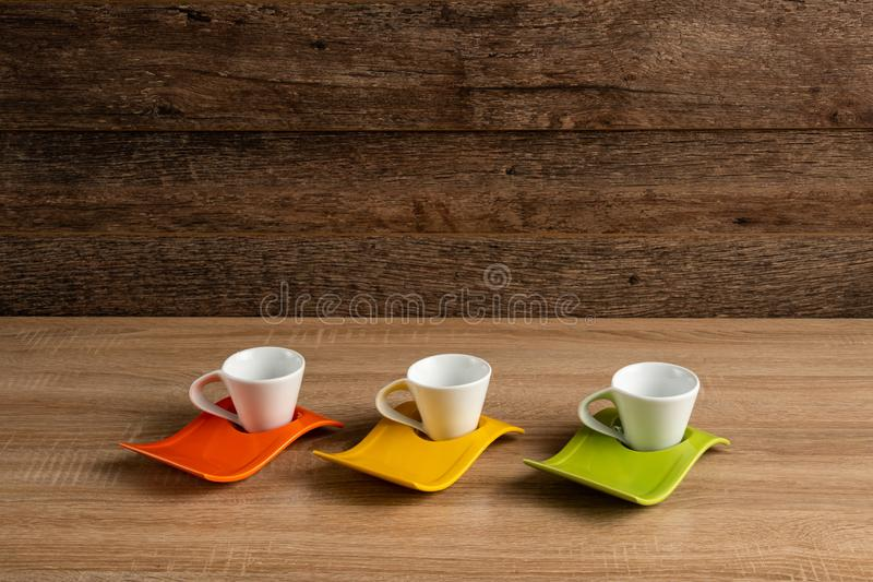 White porcelain coffee cups on a light wooden board. Dark brackground with lots of copy space above coffee cups royalty free stock photography