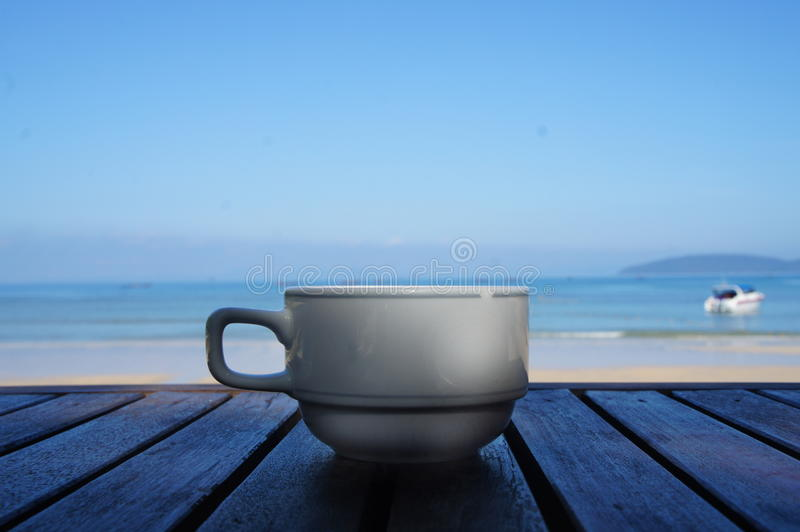 White porcelain cup of coffee on the sea background. White porcelain cup of coffee on the beautiful sea background in Thailand stock photography