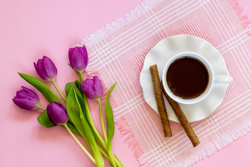 White porcelain cup with coffee, two sweet coffee rolls on saucer with wavy edge and and bouquet of pink or purple tulips. On a pink table napkin. Sweet high royalty free stock images