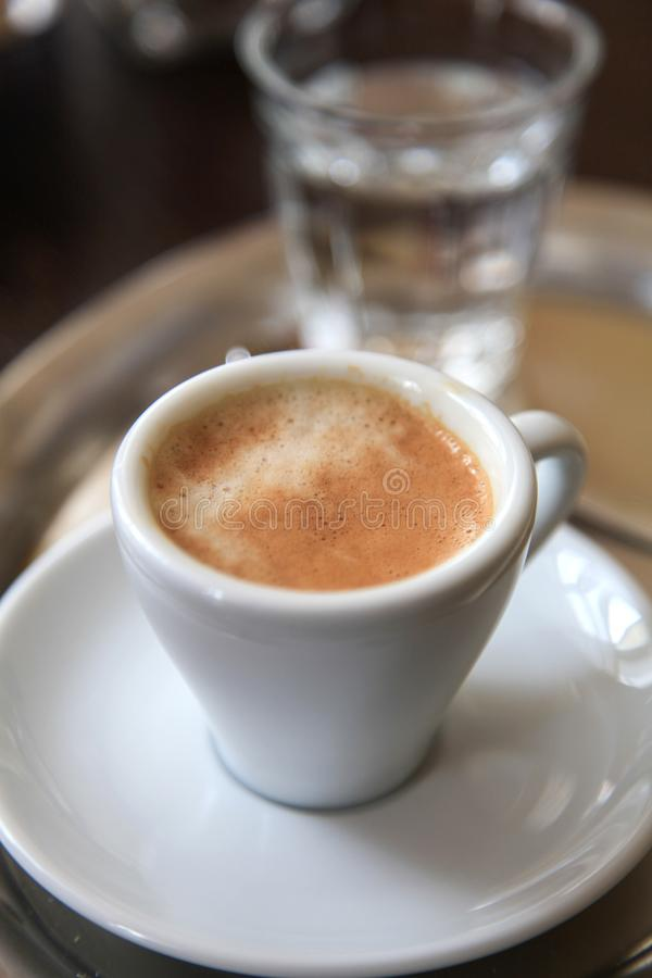 White porcelain cup with espresso and a glass of water. A white porcelain cup with espresso and a glass of water stock photos