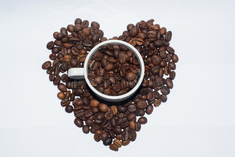 White porcelain cup full of coffee beans. Is in coffee beans in the form of a heart royalty free stock images