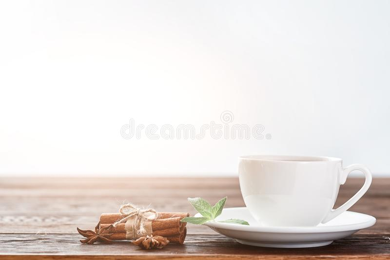 White porcelain cup of tea with cinnamon sticks, lemon, mint leaves and tea strainer royalty free stock photo