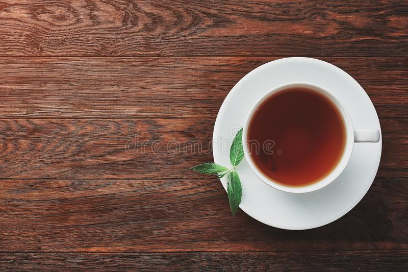 White porcelain cup of tea with cinnamon sticks, lemon, mint leaves and tea strainer royalty free stock images