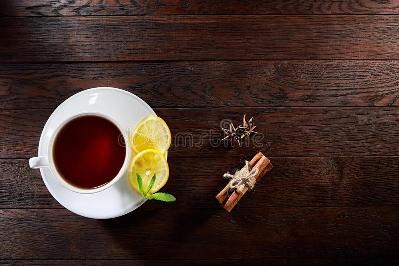 White porcelain cup of tea with cinnamon sticks, lemon, mint leaves and tea strainer on wooden rustic table. royalty free stock photos