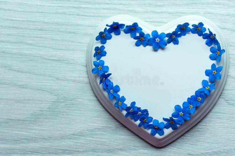White porcelain heart and light flowers laid out in the shape of a heart on a blue wooden table stock photo