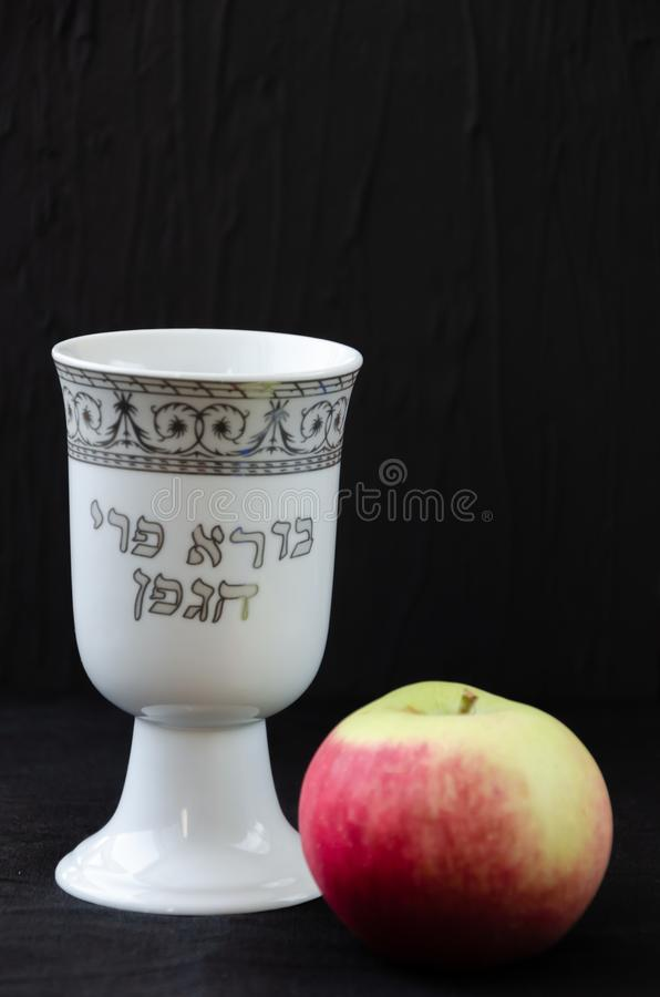 White porcelain kiddush cup and an apple on black background. The inscription in Hebrew Creator of the fruit of the vine royalty free stock photos