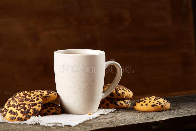White porcelain mug of tea and sweet cookies on piece of wood over wooden background, top view, selective focus royalty free stock image
