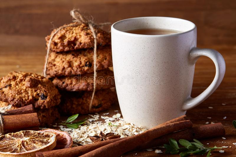 White porcelain mug of tea and sweet cookies on piece of wood over wooden background, top view, selective focus stock photos