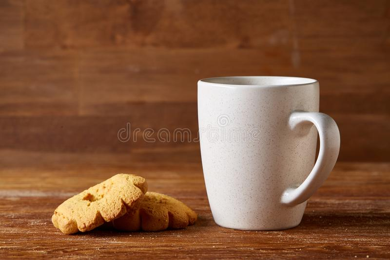 White porcelain mug of tea and sweet cookies on piece of wood over wooden background, top view, selective focus stock image