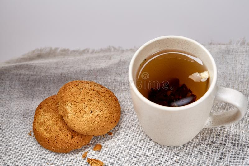 White porcelain mug of tea and sweet cookies on homespun napkin over white background, top view, selective focus stock photos