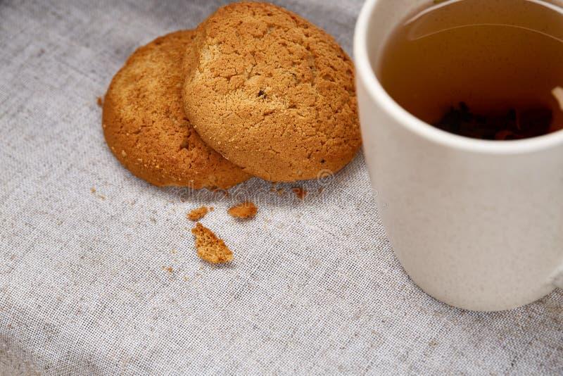 White porcelain mug of tea and sweet cookies on homespun napkin over white background, top view, selective focus stock photo