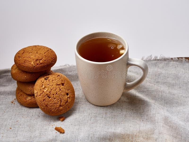 White porcelain mug of tea and sweet cookies on homespun napkin over white background, top view, selective focus royalty free stock photography