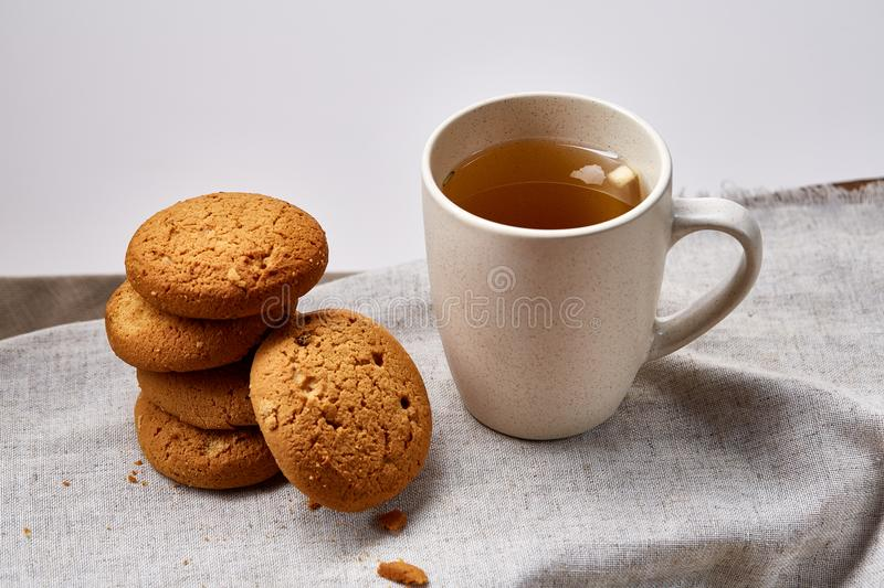 White porcelain mug of tea and sweet cookies on homespun napkin over white background, top view, selective focus royalty free stock photos