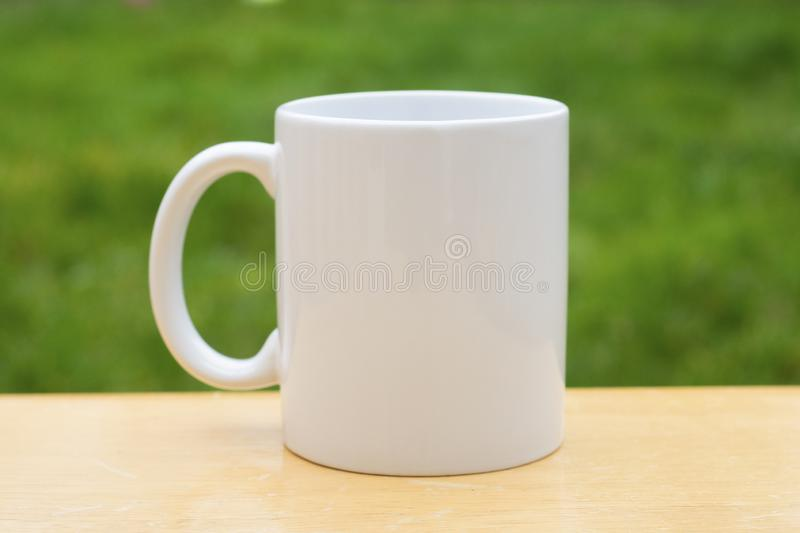 White porcelain mug cup isolated on green grass background with copy space. Coffee or tea cup. White porcelain mug cup isolated on green grass background with royalty free stock image