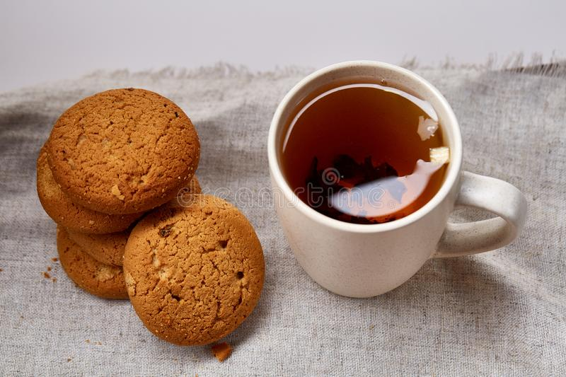 White porcelain mug of tea and sweet cookies on homespun napkin over white background, top view, selective focus stock images