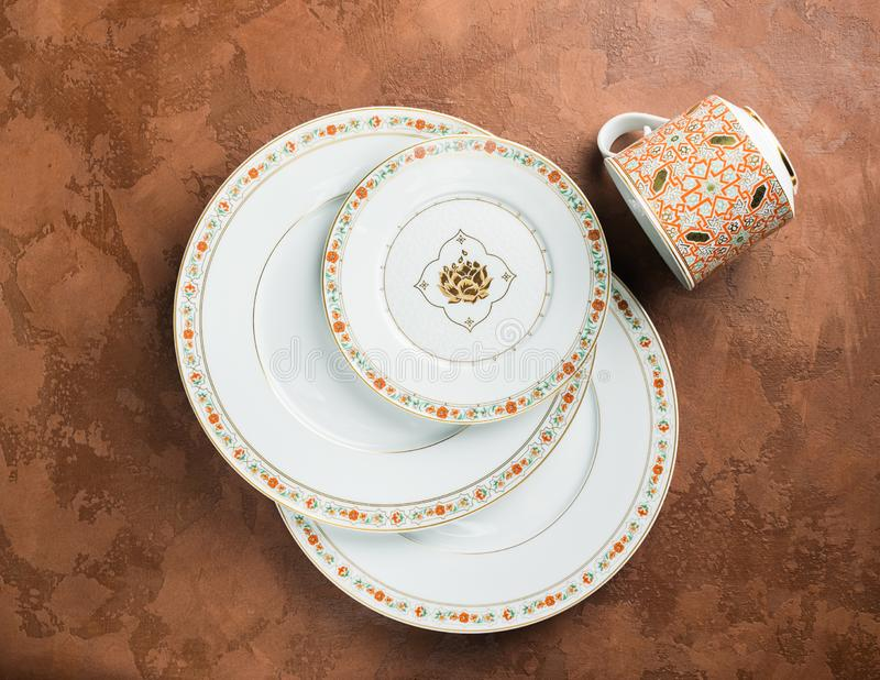 White porcelain plates of various sizes and a circle with an ornament lie on a textured brown background. Flat layout. View from above stock photography